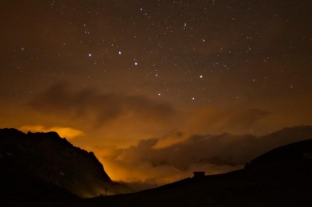 Il Grande Carro visibile sopra le nuvole diffondono il bagliore arancione delle luci di Val d'Isere.