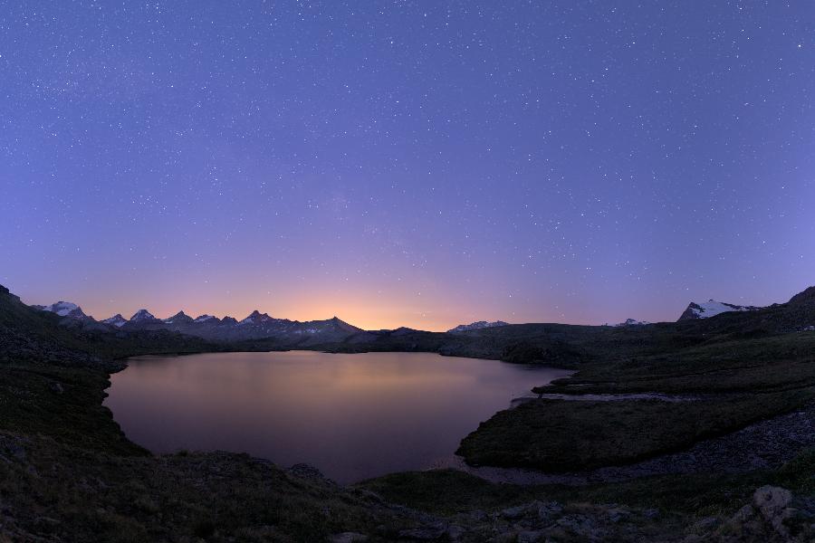 Panorama al crepuscolo dal lago Leynir sopra il colle del Nivolet. Il chiarore all'orizzonte è il prodotto dell'illuminazione artificiale degli abitati più a valle.