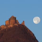 La Luna piena affianca la Sacra di San Michele illuminata dai primi raggi del Sole.