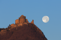 La Luna piena affianca la Sacra di San Michele illuminata dai primi raggi del Sole.