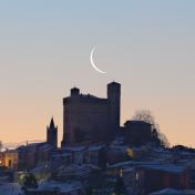 Una falce di Luna calante sorge dietro Serralunga d'Alba.