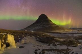 Kirkjufell e cascate accompagnati da una tenue aurora.