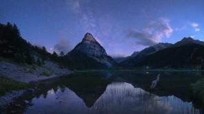 Marte, Saturno e il centro della Via Lattea si riflettono nelle acque del Lac des Sagnes al crepuscolo.