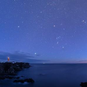 Il faro di Svörtuloft (Islanda) al crepuscolo, accompagnato dalle costellazioni di Orione e del Toro.