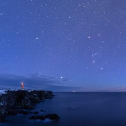 Il faro di Svörtuloft al crepuscolo, accompagnato dalle costellazioni di Orione e del Toro.