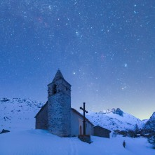 La chiesetta del villaggio di Avérole al crepuscolo con la Bessanese sullo sfondo. In cielo, le costellazioni di Toro, Auriga e Perseo e le loro nebulose a emissione.
