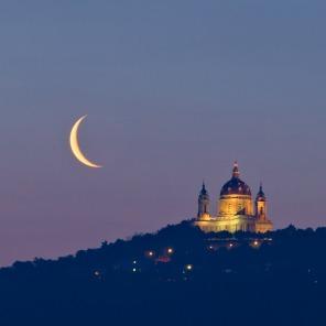Un falce di Luna calante sorge dietro Superga alle prime luci del crepuscolo mattutino.