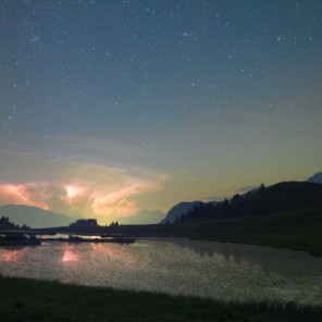 Fulmini di un temporale sulla pianura piemontese. Più in alto, sopra le nubi, il Doppio Ammasso del Perseo e la Galassia di Andromeda.