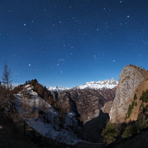 Orione e le costellazioni invernali basse sulle cime dell'alta Val Maira. Panorama al chiaro di Luna.