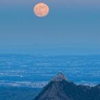 La Sacra di San Michele domina la pianura mentre sorge la Luna in eclissi di penombra.