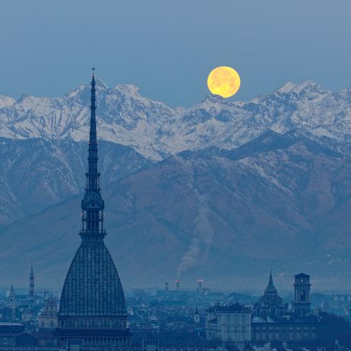 La Luna piena tramonta dietro le Alpi che circondano Torino.