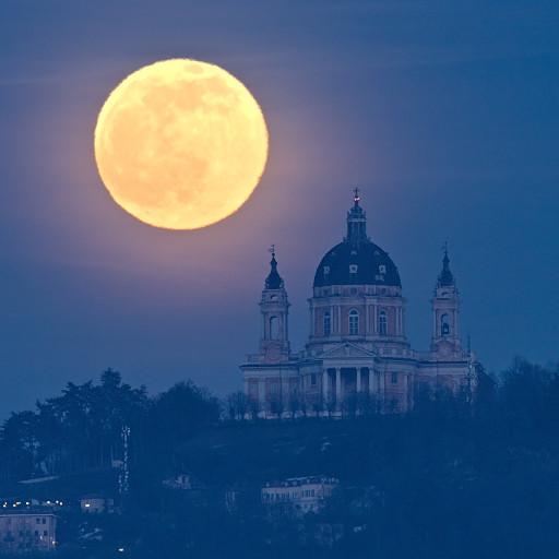 La Luna piena sorge da dietro la collina di Superga.