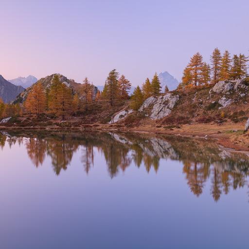Il paesaggio autunnale si specchia nel lago Nero alle luci del tramonto.